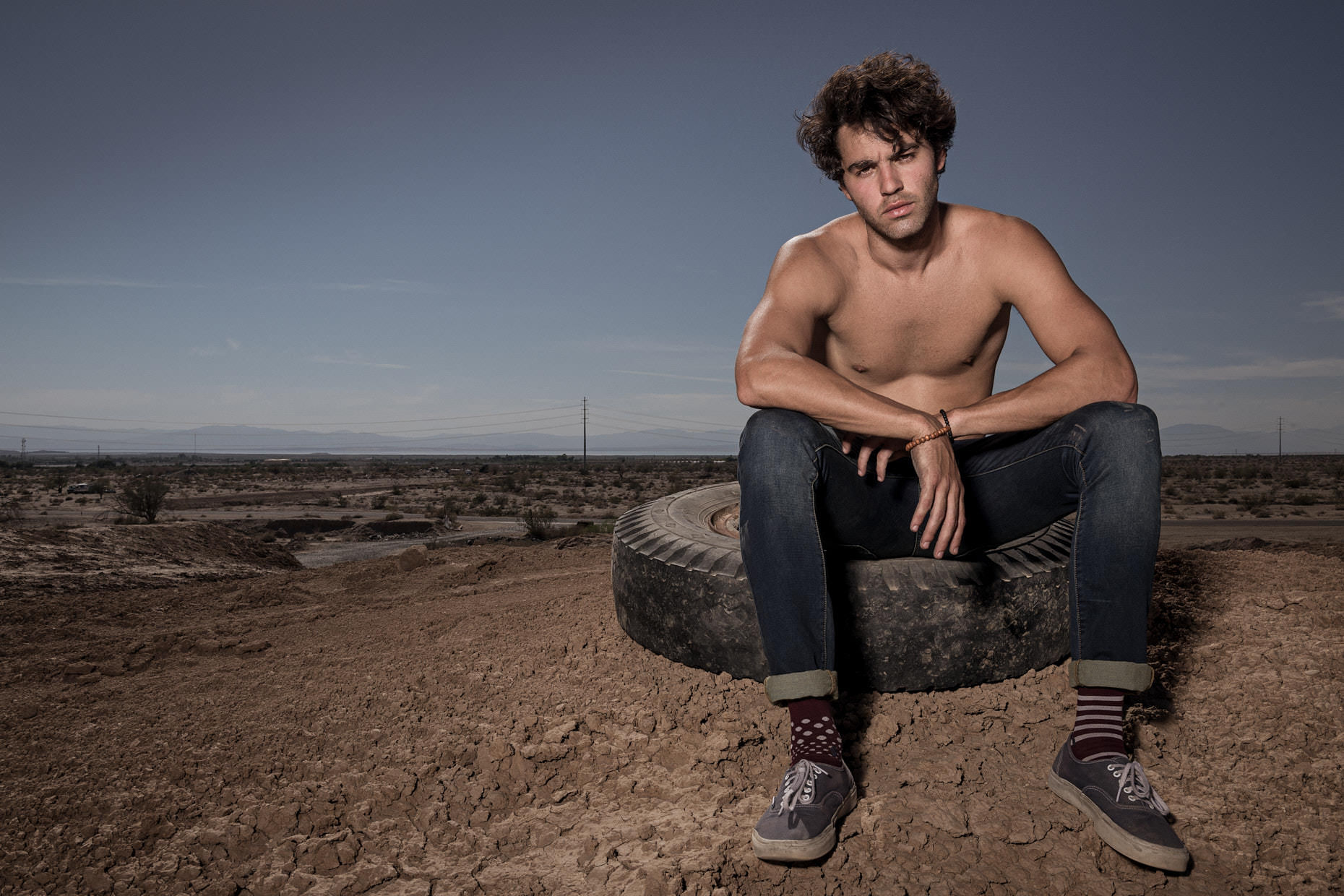 Environmental portrait of a man sitting on a tire in the California desert by photographer Jason Tracy