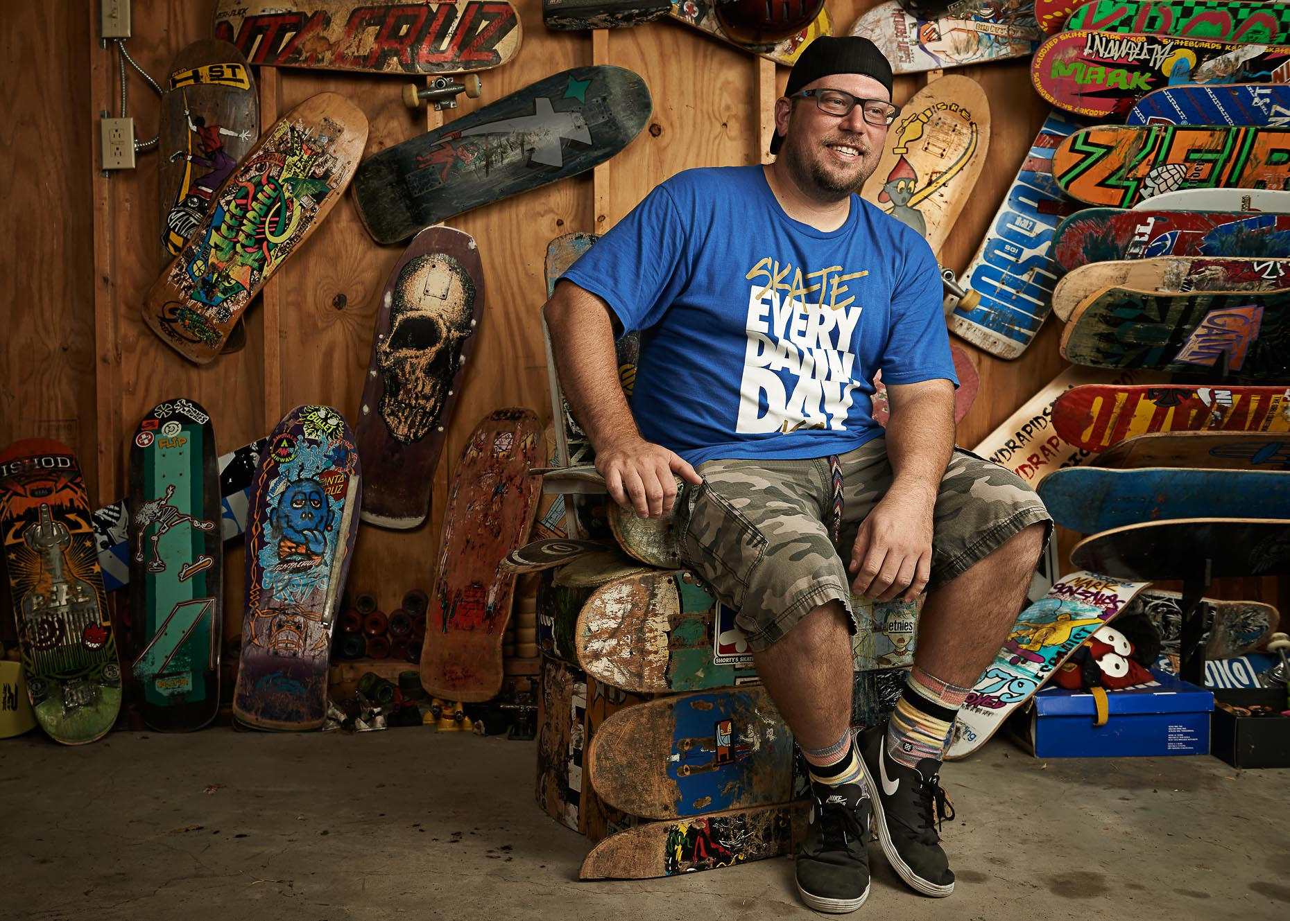 Skateboarder Brian Blancho sitting on a throne of broken skateboards